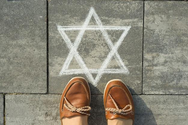 Kobiece stopy z abstrakcyjnym wizerunkiem sześcioramiennej gwiazdy, napisanym na szarym chodniku