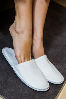 Kobiece stopy z białymi kapciami. koncepcja spa, rozpieszczanie. na białym tle.