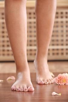 Kobiece stopy z kwiatami na podłodze