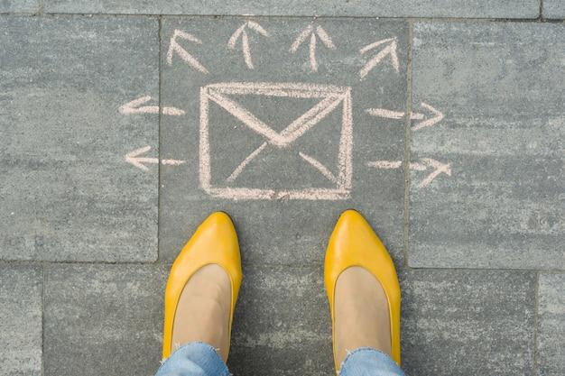 Kobiece stopy z list koperta streszczenie wiadomości ze strzałkami