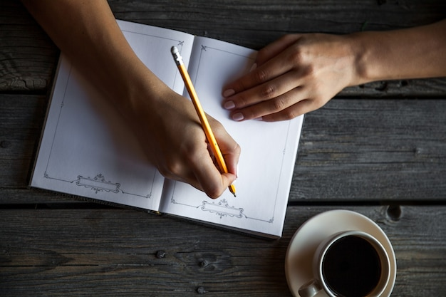 Kobiece strony przy filiżance kawy, robienie notatek.