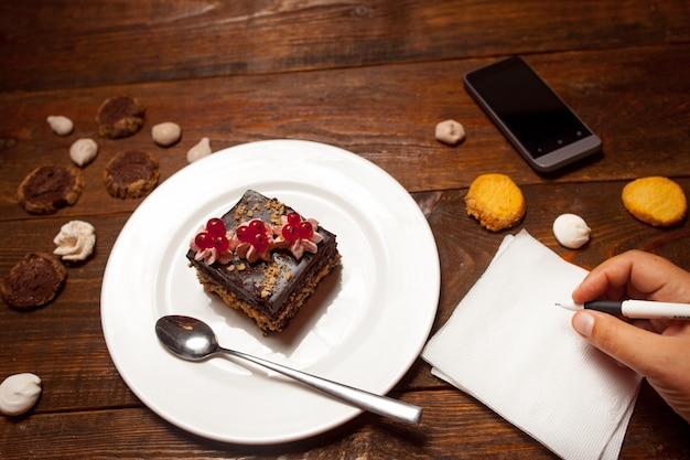 Kobiece strony robienia notatek w kawiarni z czekoladowym deserem