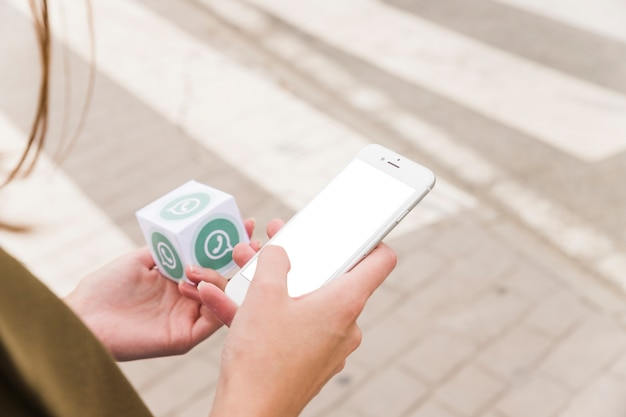 Kobiece strony za pomocą telefonu komórkowego i trzymając blok whatsapp