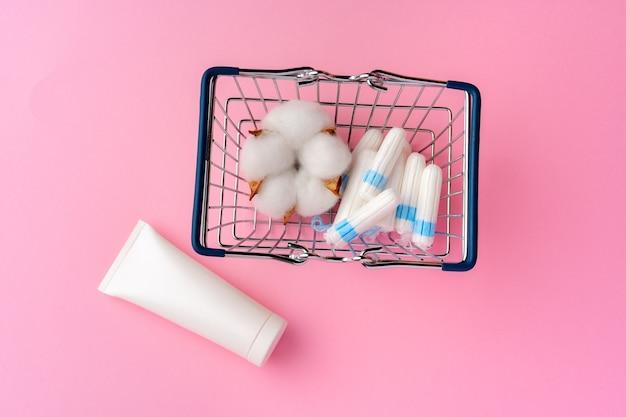 Kobiece tampony higieniczne na różowym tle papieru