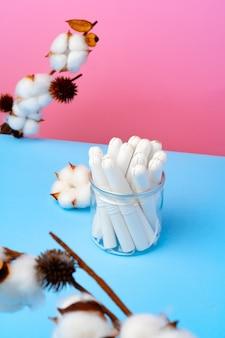 Kobiece tampony medyczne na różowej i niebieskiej powierzchni