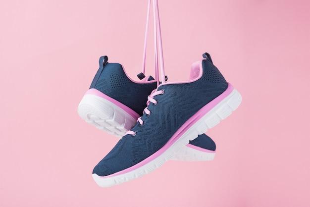 Kobiece trampki do biegania na różowym tle. moda stylowe buty sportowe, z bliska