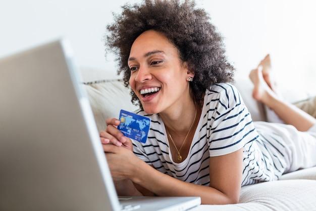 Kobiece wydatki konsumenckie na zakupy w internecie, styl życia. szczęśliwa kobieta robi zakupy online z laptopem w domu.