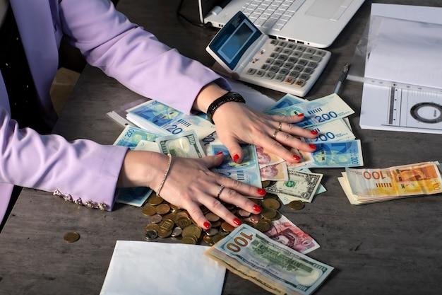 Kobiece wypielęgnowane dłonie z czerwonym lakierem do paznokci sięgają po kupę pieniędzy. dolary, funty brytyjskie i nowe szekle banknoty na stole. pojęcie sukcesu, chciwości i korupcji, żądzy pieniędzy