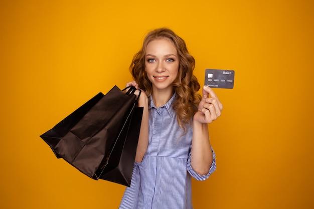 Kobiece zakupy. młoda kobieta trzyma czarne torby papierowe i kartę kredytową na białym tle nad żółtym studio.