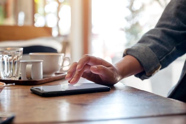 Kobiecej dłoni, dotykając ekranu smartfona z filiżanką kawy na drewnianym stole w kawiarni