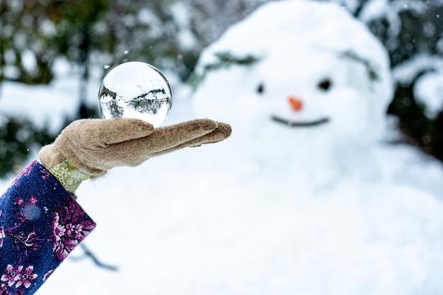 Kobiecej dłoni trzymającej kryształową kulę obok bałwana.