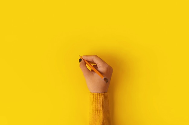 Kobiecej dłoni trzymającej ołówek na żółtym tle