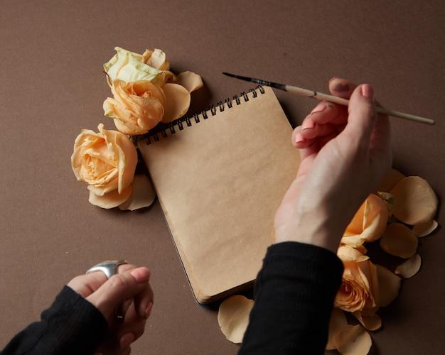 Kobiecej dłoni trzymającej pióro nad pamiętnikiem lub notatnikiem do robienia notatek dotyczących walentynek.
