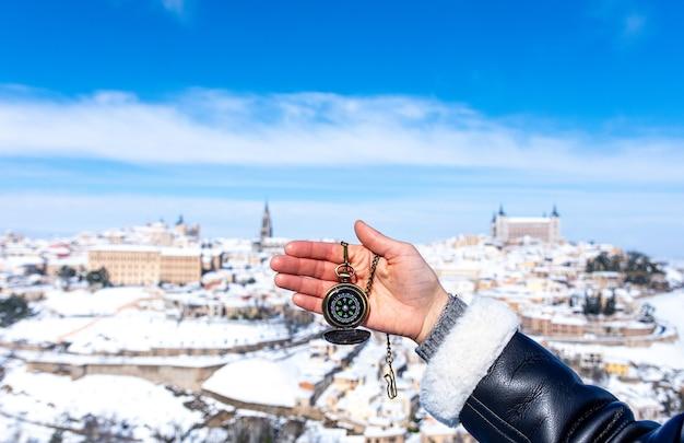 Kobiecej dłoni trzymającej złoty kompas. panoramiczny śnieżny widok na miasto toledo w tle.