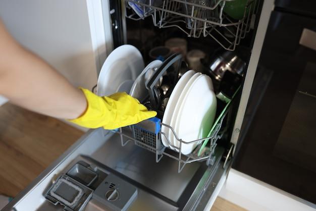 Kobiecej dłoni w gumowej rękawicy wkłada naczynia do zmywarki