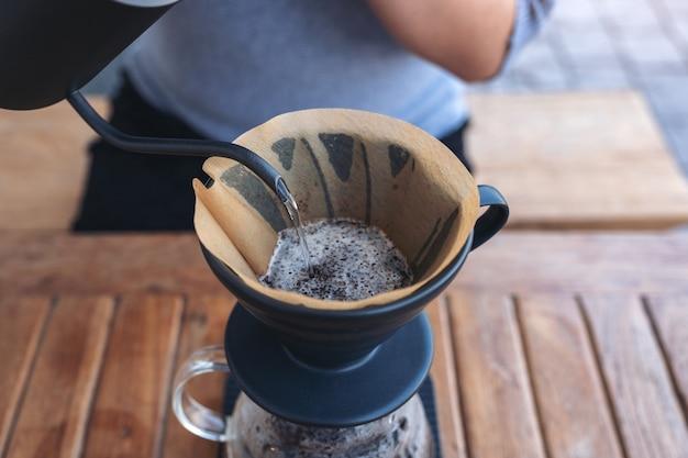 Kobiecej dłoni wlewając gorącą wodę, aby zrobić kroplówkę kawy na vintage drewnianym stole