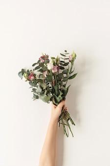 Kobiecej ręki trzymającej bukiet kwiatów róż na białej ścianie