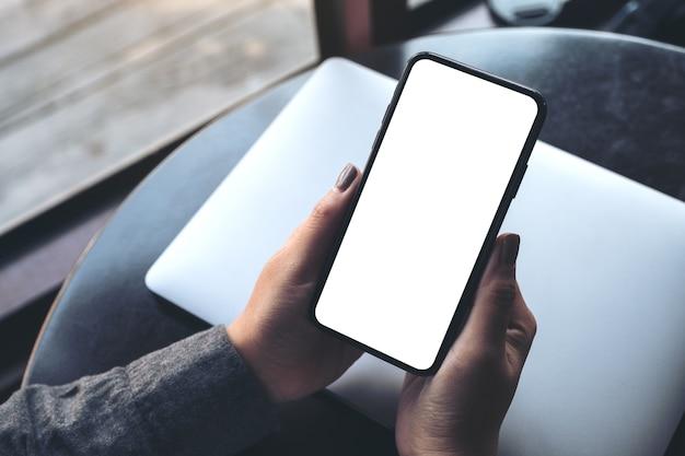 Kobiecej ręki trzymającej czarny telefon komórkowy z pustym biały ekran pulpit