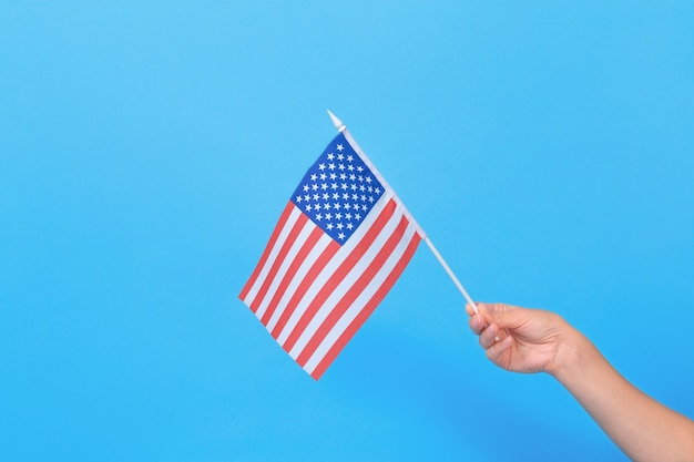 Kobiecej ręki trzymającej małą amerykańską flagę na niebieskim tle. miejsce na tekst.