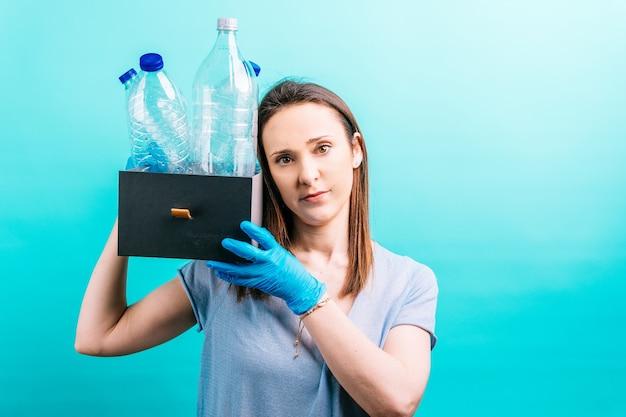 Kobiecej ręki trzymającej pudełko z plastikowymi butelkami do recyklingu. koncepcja recyklingu. troska o środowisko