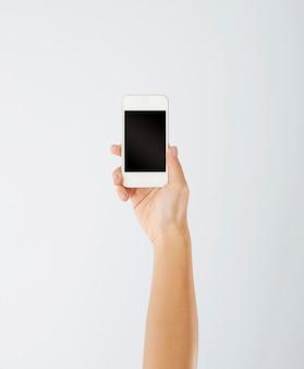 Kobiecej ręki trzymającej współczesny telefon komórkowy