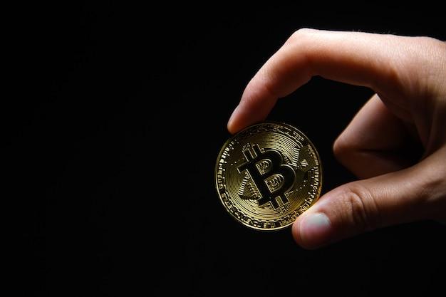 Kobiecej ręki trzymającej złote bitcoin na czarnym tle