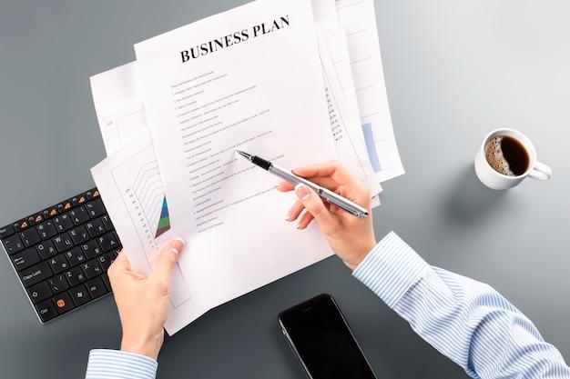 Kobiecy biznesplan i długopis. sekretarz przegląda biznesplan. mogą być błędy. potrzebujesz czasu, aby to naprawić.