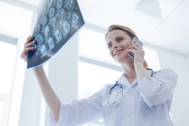 Kobiecy inteligentny radiolog pozytywny pracujący w gabinecie rentgenowskim, badający rentgen mózgu i używający cyfrowego gadżetu do rozmowy