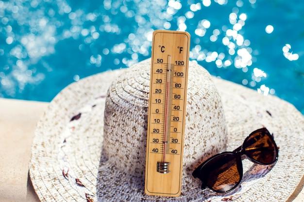 Kobiecy kapelusz, termometr i okulary przeciwsłoneczne leżące przy basenie. koncepcja upałów, lata i wakacji