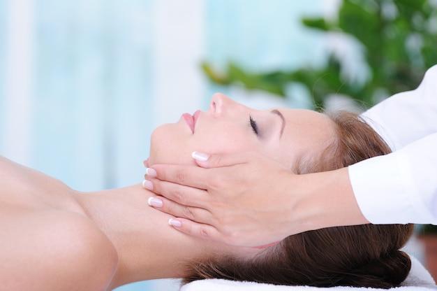 Kobiecy masaż twarzy w gabinecie kosmetycznym - zbliżenie profilu
