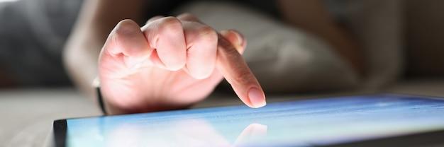 Kobiecy palec nad dołączonym tabletem wprowadzenie sieci społecznościowych za pośrednictwem aplikacji