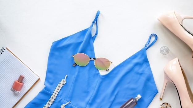 Kobiecy strój na stole, okulary, niebieska sukienka, buty i dekoracje. widok z góry