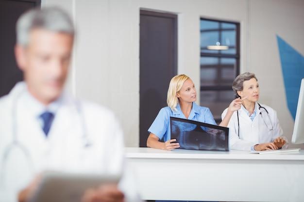 Kobiet lekarki z promieniowaniem rentgenowskim podczas pracy przy biurkiem komputerowym
