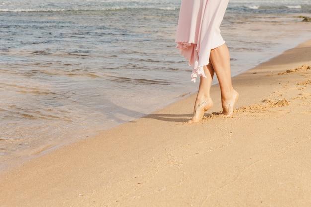 Kobiet nogi chodzi na plażowym piasku