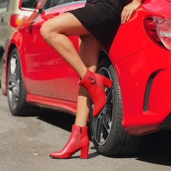 Kobiet nogi w czerwonych butach opiera przeciw samochodowi