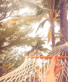 Kobiet nogi w hamaku na tle morza, drzewek palmowych i zmierzchu