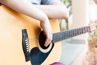 Kobiet ręki z gitarą akustyczną wewnątrz relaksują poczta