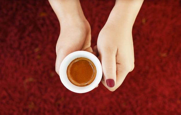 Kobiet ręka trzyma filiżankę kawy na czerwonym dywanie
