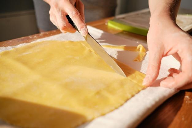 Kobiet ręki, ciie ciasto w świetle słonecznym