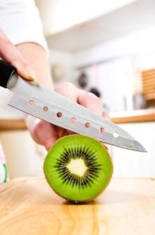 Kobiet ręki ciie świeżego kiwi na kuchni