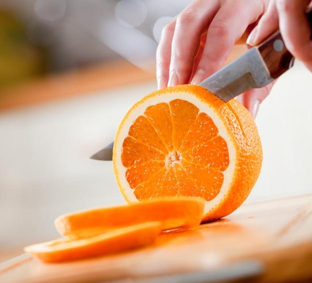Kobiet ręki ciie świeżej pomarańcze na kuchni