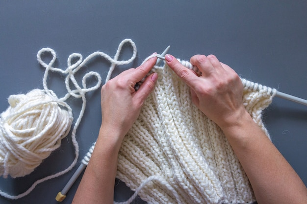 Kobiet ręki dzia białego wełny przędzy wzór. zbliżenie zdjęcie poziome. kreatywne rękodzieło niezależne
