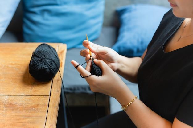 Kobiet ręki dzia szydełkowy relaksować przy kawiarnią.