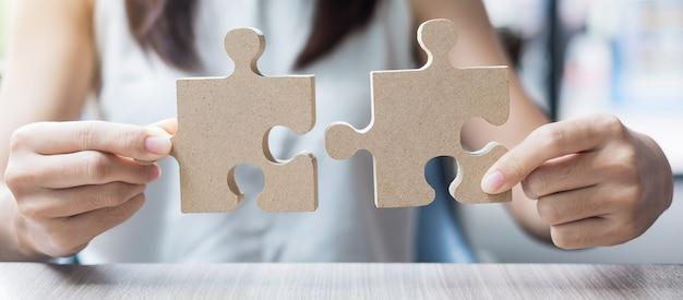 Kobiet ręki łączy pary łamigłówkę nad stołem, bizneswoman trzyma drewnianą wyrzynarkę wśrodku biura. rozwiązania biznesowe, misja, cel, sukces, cele i strategie