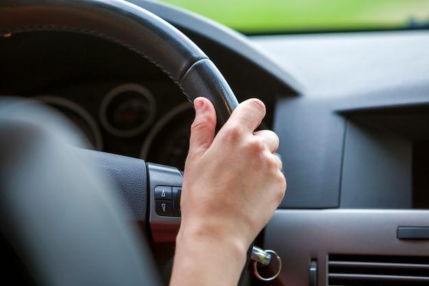 Kobiet ręki na kierownicie jedzie samochód.