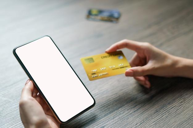 Kobiet ręki trzyma cradit kartę i smartphone pustego ekran