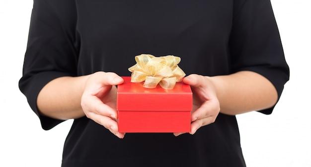 Kobiet ręki trzyma czerwonego prezenta pudełko. kobiety waring czerni suknię na białym tle
