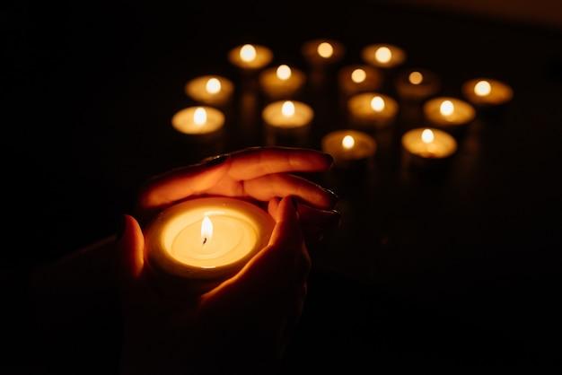 Kobiet ręki trzyma płonącą świeczkę. wiele płomieni świec świecących. zbliżenie.