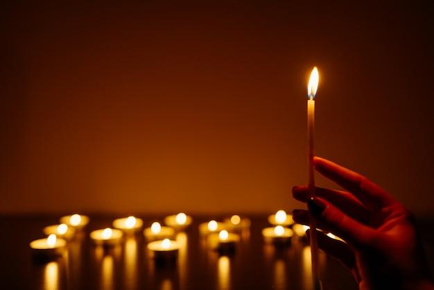 Kobiet ręki trzyma płonącą świeczkę. wiele płomieni świec świecących.