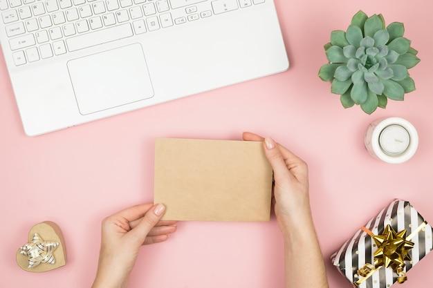Kobiet ręki trzyma rzemiosło kopertę z copyspace na różowym pastelowym stołowym odgórnym widoku. kompozycja płasko świeckich na walentynki.